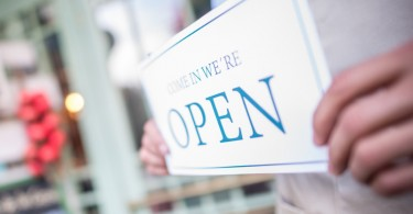 Waiter or business owner holding an open sign at a restaurant welcoming customers